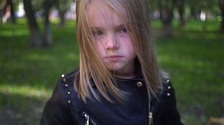 Serious little blonde girl wearing a leather jacket looking at camera. Zoom out slow motion close shot