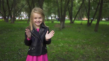 Happy cute little blonde girl wearing a leather jacket smiling, looking at camera and clapping. Handheld slow motion medium shot