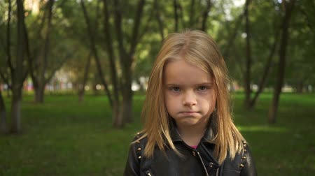 Serioius little blonde girl wearing a leather jacket is fed up. She is standing in a park on a summer day. Handheld slow motion establishing shot