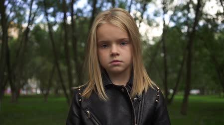 Serious and cute blonde girl wearing a leather jacket looking at camera. Handheld slow motion medium shot