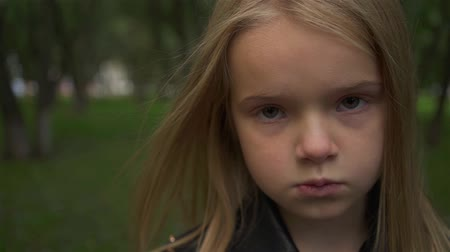 Serious and cute blonde girl wearing a leather jacket looking at camera standing in a park. Handheld slow motion close up shot