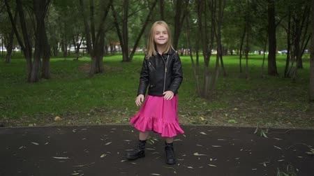 inspiráló : Cute little blonde girl wearing a leather jacket and a pink dress is dancing while standing in a park on a summer day. Handheld slow motion medium shot Stock mozgókép