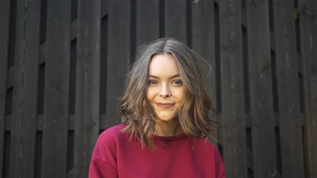 Attractive young woman wearing a red sweatshirt smiling and looking at camera. A tall wooden fence background. Handheld slow motion establishing shot Stock Footage