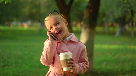 Cute little girl in pink smiling and talking on her smartphone while being in a park. She is holding a cup of coffee. Handheld slow motion establishing shot