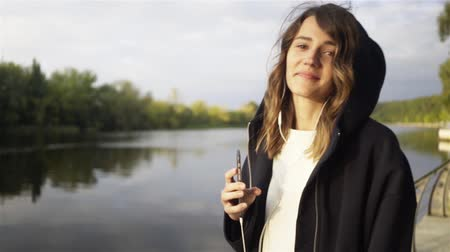 Positive young woman wearing a black hoodie listening to the music and dancing on a river bank. Left to right pan slow motion establishing shot Stock Footage