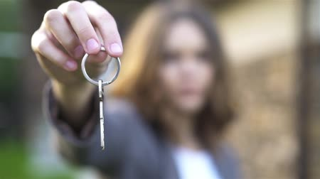 Unrecognizable young woman showing the key from her new house in the suburbs. Mortgage concept. Handheld slow motion medium shot