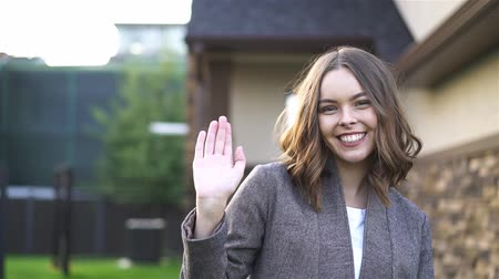 Attractive young woman wearing a suit smiling and waving her hand in greeting while looking at camera. A subirbian street background. Handheld slow motion establishing shot