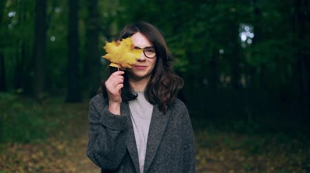 Attractive young woman wearing a gray coat and glasses is playing with maple leaves and laughing in a park on an autumn day. Handheld slow motion medium shot
