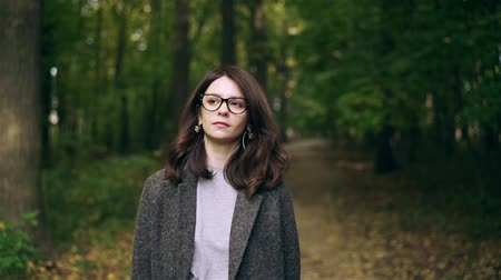 Calm dark haired businesswoman wearing glasses and a coat is walking in an autumn forest or a park. Slow motion tracking medium shot Stock Footage