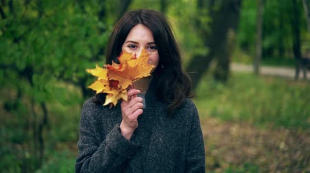 Beautiful young woman waving maple leaves in front of her face standing in an autumn park. Locked down slow motion medium shot Stock Footage