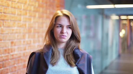 Calm and attractive young woman looking at camera and saying no as if disgusted by a request while standing in a building corridor with brick walls. Handheld slow motion medium shot