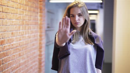 Calm and attractive young woman looking at camera, saying no and stretching her hand to stop somebody off camera while standing in a building corridor with brick walls Handheld slow motion medium shot