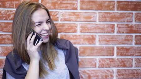 Beautiful young girl in a T shirt and a hoodie talking on the phone standing near a brick wall and smiling. Handheld slow motion medium shot Stock Footage