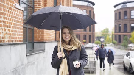 Cheerful blonde businesswoman wearing a coat and a scarf is standing with a coffee under an umbrella in a street. Handheld slow motion medium shot
