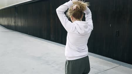 Rear view of a woman jogger with blonde curly hair using a hairband and starting her workout in the street. Handheld real time medium shot