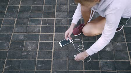 cipőfűző : Top view of an unrecognizable jogger woman with blonde hair tying her shoelace, taking her smartphone with headphones and starting to run in a street. Handheld slow motion close up shot