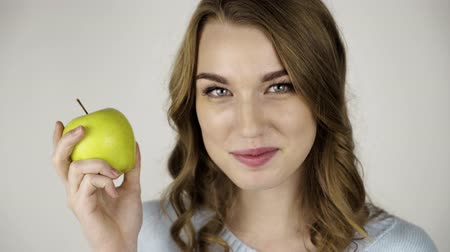 Seductive fair haired woman in gray holding a green juicy apple and flirting. Locked down real time close up shot