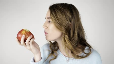 Seductive fair haired woman in gray biting a red juicy apple and chewing it. She is looking at you and licking her lips. Locked down real time medium shot Stock Footage