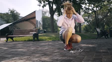 Woman jogger with blonde curly hair using a hairband and starting her workout in the street. Handheld slow motion medium shot Stock Footage