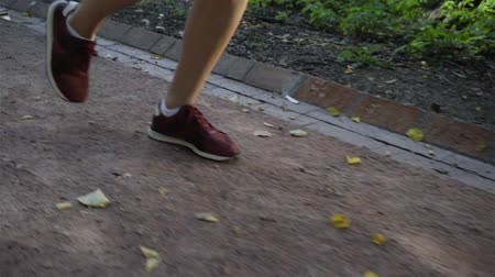 Close up of legs of an unrecognizable jogger woman in dark red running shoes moving on a road in a park on a sunny day. Tracking slow motion close up shot