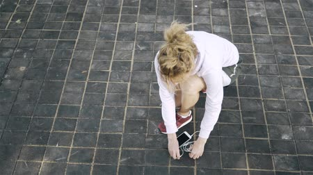 Top view of an unrecognizable jogger woman with blonde hair tying her shoelace, taking her smartphone with headphones and starting to run in a park. Handheld slow motion close up shot Stock Footage