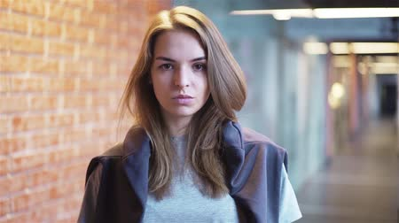Calm and attractive young woman looking at camera and saying no while standing in a building corridor with brick walls. Handheld slow motion medium shot Stock Footage
