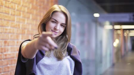 Beautiful young woman looking at camera, smiling and pointing with her finger. She is calling the viewer while standing in a building corridor with brick walls. Handheld slow motion medium shot