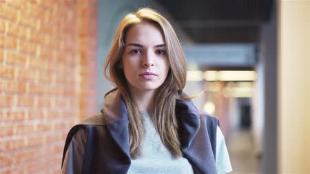 Calm and beautiful young woman looking at camera and blinking while standing in a building corridor with brick walls. Handheld slow motion medium shot Stock Footage