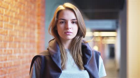 Calm and beautiful young woman looking at camera and smiling while standing in a building corridor with brick walls. Handheld slow motion medium shot Stock Footage