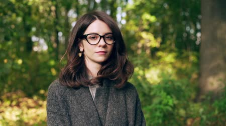 Calm attractive businesswoman wearing a gray coat and glasses is turning her head to look at the camera. An autumn park background. Handheld slow motion medium shot Stock Footage