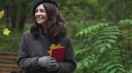 Happy young brunette woman wearing a coat, gloves and a beret is holding a book with maple leaves and smiling standing under falling leaves. Handheld slow motion medium shot Stock Footage