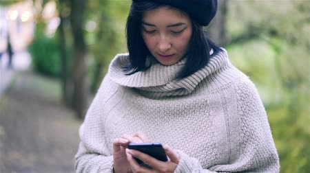 Attractive young Asian woman wearing a sweater and a beret is holding her smartphone and web surfing. Handheld slow motion close up shot