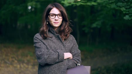 Calm dark haired businesswoman wearing glasses and a thick coat is standing in an autumn forest or a park and smiling. Slow motion locked down medium shot