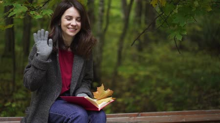 Cheerful young brunette wearing a coat and gloves is holding a book sitting on a bench in an autumn park and waving her hand. Handheld slow motion medium shot