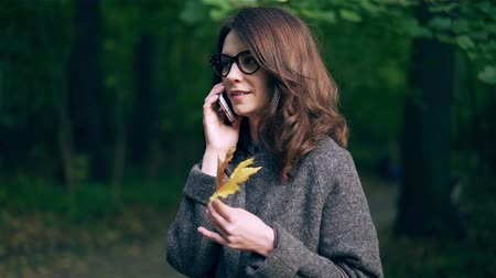 Attractive young woman wearing a gray coat is holding maple leaves and talking on her smartphone in autumn park. Handheld slow motion medium shot