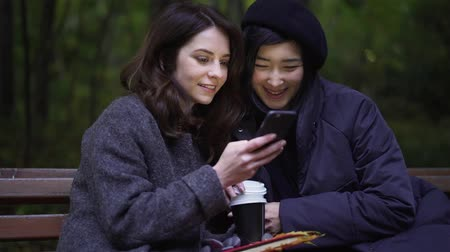 Two attractive young women wearing coats are looking at a smartphone and talking while sitting on a bench in an autumn park. Handheld slow motion medium shot
