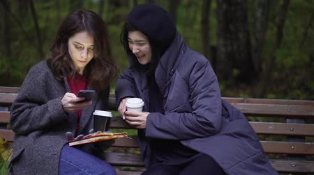 Two beautiful young women wearing coats are looking at a smartphone and talking while sitting on a bench in an autumn park. Handheld slow motion medium shot