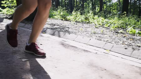 dres : View of legs of an unrecognizable young woman jogging downhill in a park on a summer day. Tracking slow motion close up shot