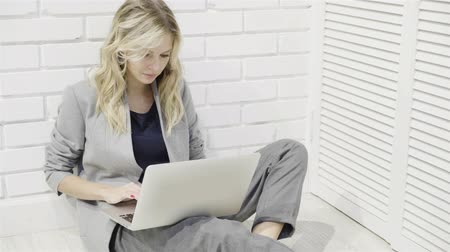 motive : Pretty blonde woman in a gray suit sitting on the floor and typing on her laptop. Left to right pan real time medium shot