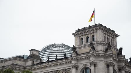 bundestag : Real time locked down close up shot of the national flag waving on the wind at the top of The German Parliament and the Deutsche Bundestag in Berlin. Stock Footage