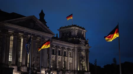 bundestag : BERLIN - AUGUST 21: German and EU flags waving in the night on The German Parliament and the Deutsche Bundestag in Berlin, August 21, 2017. Nighttime. Locked down real time establishing shot Stock Footage