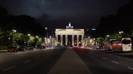 triumphal arch : BERLIN - AUGUST 21: Real time locked down medium shot of The Brandenburg Gate, August, 21, 2017 in Potsdam, Germany. It is a famous tourist place. Night time. Cars and an ambulance