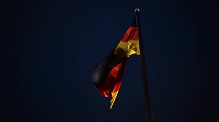 main : German national flag waving against a night sky background. Concept of tourism and national spirit. Locked down real time close up shot