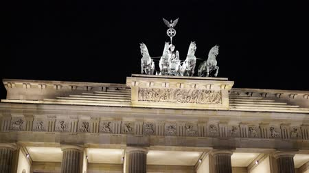 triumphal arch : Real time left to right close up shot of The Brandenburg Gate in Potsdam, Germany. It is a famous tourist place with busy people traffic. Night time