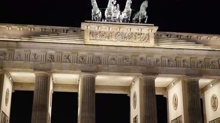 triumphal arch : Real time tilt up close up shot of the Brandenburg Gate in Potsdam, Germany. It is a famous tourist place with busy people traffic. Night time