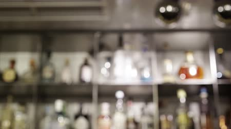 loungebar : Modern bar interior with collection of bottles on the shelves. Tilt down real time establishing shot, blurred