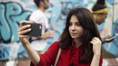 descartável : Beautiful young woman with dark hair wearing a dark red shirt is taking a selfie near the Berlin wall on a summer day. People walking in the background Handheld real time medium shot