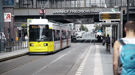 csomópont : BERLIN - AUG 21: Real time locked down shot of an arriving bright yellow tram in Friedrichstrasse in Berlin, Germany. People walking. August 21, 2017 in Berlin, Germany.