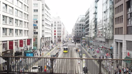tramwaj : BERLIN - AUG 21: Real time locked down shot of Friedrichstrasse in Berlin, Germany. People walking, yellow tram is passing by on a bright summer day, August 21, 2017 in Berlin, Germany. Wideo