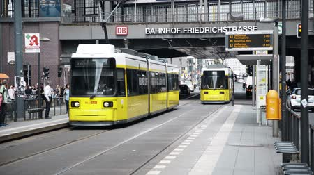 friedrichstrasse : BERLIN - AUG 21: Real time locked down shot of two yellow trams going in different directions in Friedrichstrasse in Berlin, Germany. August 21, 2017 in Berlin, Germany. Stock Footage